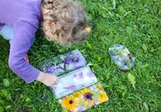 Little girl playing with ice cubes with flowers on green grass at summer.