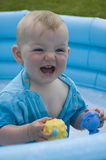 Child playing in the inflatable pool. Child paddling and playing with rubber toys in the inflatable blue pool Royalty Free Stock Photos