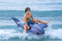 Child playing with inflatable shark in waves. Joung boy child summer vacation at sea and playing with inflatable shark toy in waves - freedom, vacation, fun Royalty Free Stock Image