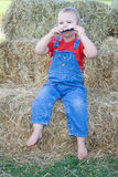 Child playing instrument. A happy toddler girl dressed in a red shirt and denim overalls playing a harmonica while sitting on straw bales barefoot stock images