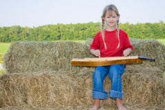Child playing instrument. A happy and smiling farm girl dressed in a red shirt and bluejeans playing the mandolin while sitting on straw bales barefoot Stock Photos