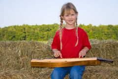 Child playing instrument. A happy and smiling farm girl dressed in a red shirt and bluejeans playing the mandolin while sitting on straw bales with the Royalty Free Stock Images