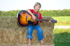 Child playing instrument. A happy farm girl dressed in a red shirt and bluejeans strumming the guitar and singing a song while sitting on straw bales with bare Royalty Free Stock Photo