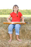 Child playing instrument. A happy and smiling farm girl in braids and dressed in a red shirt and blue jeans and barefoot playing a mandolin while sitting on Royalty Free Stock Images