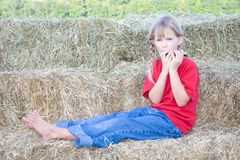 Child playing instrument. A young farm girl dressed in a red shirt and denim jeans playing the harmonica while sitting on straw bales in her bare feet Stock Photos