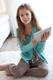 Child playing on ipad. Tablet pc sitting on a carpet at home Stock Image