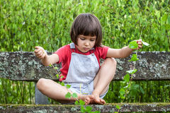 Child playing with ivy stems to learn nature in garden Stock Image