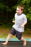 Child playing while jumping on trampoline outdoors Stock Images