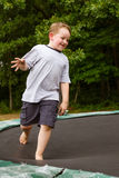 Child playing while jumping on trampoline outdoors Royalty Free Stock Photo