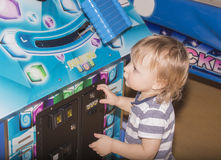 Child playing on the kids game machine at an amusement park Royalty Free Stock Photos