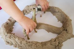 Child playing with kinetic sand. Baby`s sensory experiences. Toddler`s hands touching the sand stock images