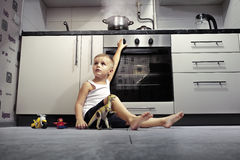 Child playing in the kitchen with a gas stove. Accident prevention. The child unattended playing in the kitchen with a gas stove Royalty Free Stock Images