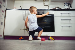 Child playing in the kitchen with a gas stove. Stock Image