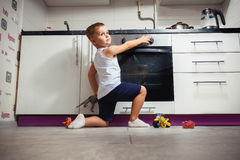 Child playing in the kitchen with a gas stove. Accident prevention. The child unattended playing in the kitchen with a gas stove. without retouch Stock Images