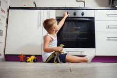 Child playing in the kitchen with a gas stove. Accident prevention. The child unattended playing in the kitchen with a gas stove. without retouch Stock Photos