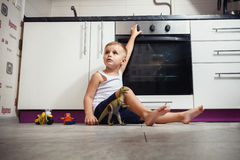 Child playing in the kitchen with a gas stove. Stock Photos