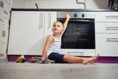 Child playing in the kitchen with a gas stove. Accident prevention. The child unattended playing in the kitchen with a gas stove. without retouch Royalty Free Stock Photos