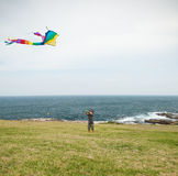 Child playing with a kite on a beach Royalty Free Stock Image