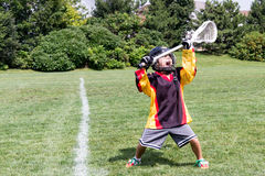 Child playing lacrosse screams in celebration joy while holding Stock Photography