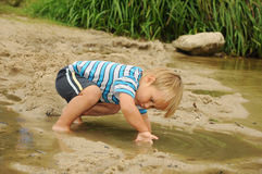 Child playing by lake Royalty Free Stock Image