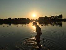 Child playing into a lake