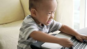 Child playing with laptop computer stock footage