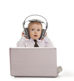 Child playing with laptop and listening to music. Funny child playing with laptop and listening to music in headphones Stock Photos