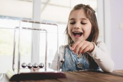 Child Playing and Learning with Newton`s Cradle. In Business Office stock image