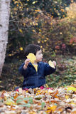 Child playing with leaves Stock Images