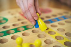 Child playing Ludo board game. Close-up view Stock Images