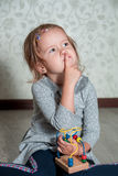 Child playing with maze. Little girl thinking  a finger near the mouth. Educational toy. Stock Photos