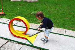 Child playing mini golf. Child trying to score at mini golf game Royalty Free Stock Image