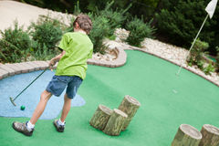 Child playing miniature golf royalty free stock image