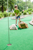 Child Playing Miniature Golf. Seven year old boy playing miniature golf in the summer Stock Photos