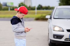 Child playing mobile games on smartphone on the street Royalty Free Stock Photos