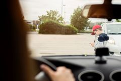 Child playing mobile games on smartphone on the street. Child busy playing the smartphone mobile games does not pay attention to the moving car. Boy child Royalty Free Stock Photo