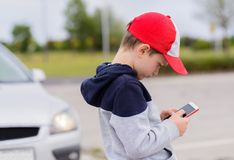 Child playing mobile games on smartphone on the street Royalty Free Stock Images