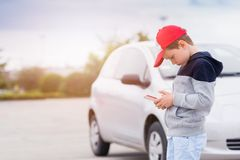 Child playing mobile games on smartphone on the street. Child busy playing the smartphone mobile games does not pay attention to the moving car. Boy child Stock Image