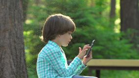 Child playing with mobile phone outdoors in green park summer. Kid using wi-fi. Cute happy boy writing texting sms on. Smartphone, touch screen. Gadgets stock footage