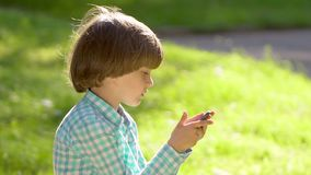 Child playing with mobile phone outdoors in green park summer. Kid using wi-fi. Cute happy boy writing texting sms on. Smartphone, touch screen. Gadgets stock video footage