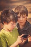 Child playing mobile phone outdoors stock photo
