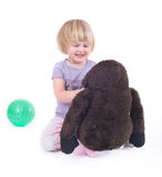 Child playing with monkey doll Stock Images