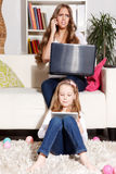 Child playing while mother is working Stock Photography