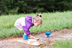 Child Playing in Mud Puddle Stock Images