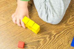 Child is playing with multicolored cubes on wooden floor Royalty Free Stock Photos