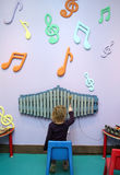 Child Playing Music. A child sits in front of a xylophone and plays music with notes on the wall Stock Image