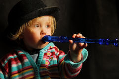 Child playing Music on Flute. A young blond girl plays a blue flute Royalty Free Stock Photos