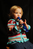 Child playing music on flute. A young blond girl plays a blue flute Stock Photos