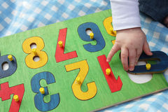 Child playing with number puzzle stock photography