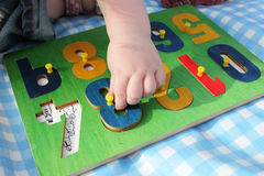 Child playing with number puzzle Royalty Free Stock Images